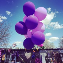 Purple balloons at the memorial fence at Paisley Park